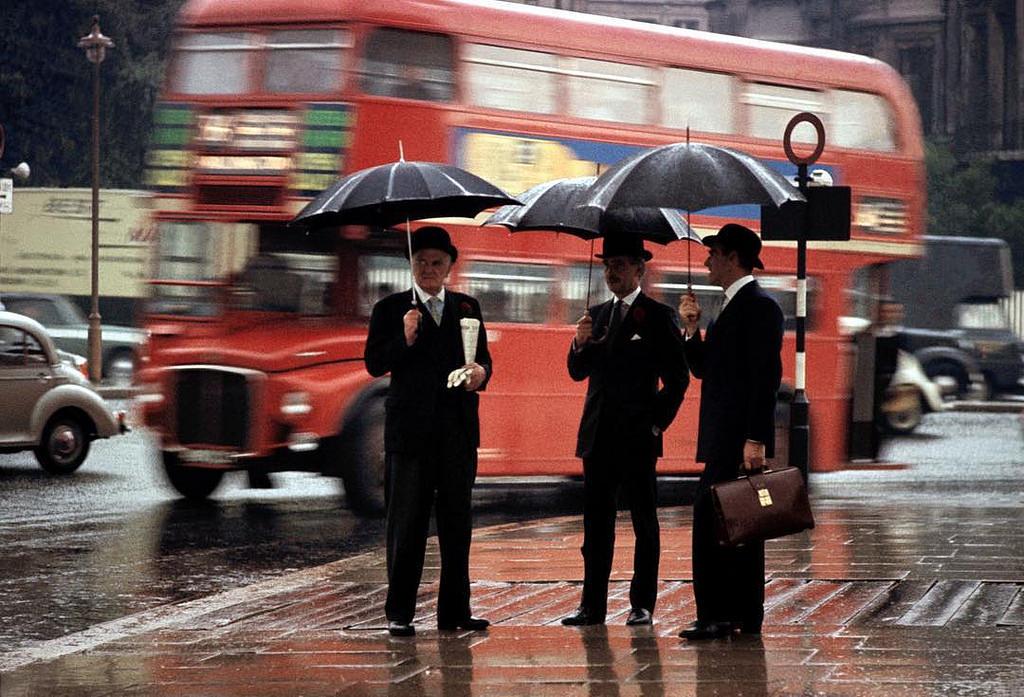Three gentlemen wait in the rain on Hyde Park corner in London, 1964