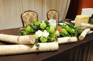 和装を考え木の温もりを入れた披露宴会場のお花